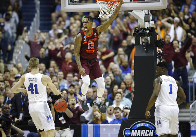 Virginia Tech guard Ahmed Hill (13) reacts after scoring on Duke forwards Jack White (41) and Zion Williamson (1) during the first half of an NCAA men's college basketball tournament East Region semifinal in Washington, Friday, March 29, 2019. (AP Photo/Patrick Semansky)