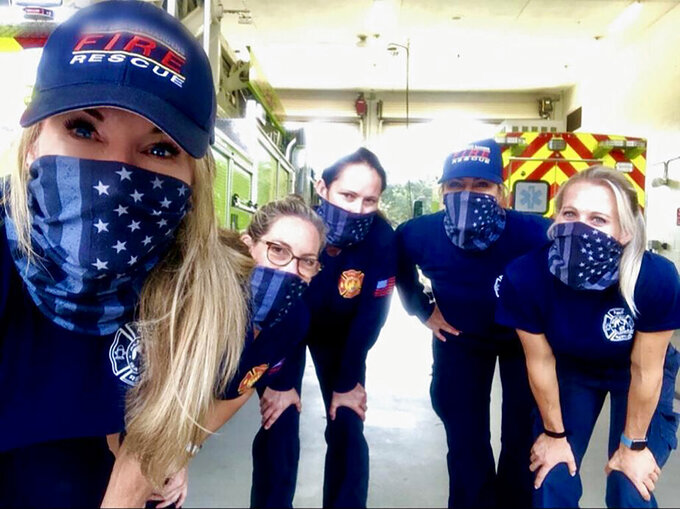CORRECTS PHOTOGRAPHER TO JULIE DUDLEY - In this September 2020 photo provided by Palm Beach Gardens Fire and Rescue, firefighters from left to right, Julie Dudley, Sandi Ladewski, Monica Marzullo, Krystyna Krakowski and Kelsey Krzywada pose at their station in Palm Beach Gardens, Fla. The women who made history by working an entire firefighting shift with no men are still thriving at their fire department in Florida months later. The members of the team at Palm Beach Gardens Fire Rescue say they've succeeded in a heavily male-dominated profession for a couple of reasons. One is that their male colleagues and supervisors have enthusiastically supported them.  (Julie Dudley/Palm Beach Gardens Fire and Rescue via AP)