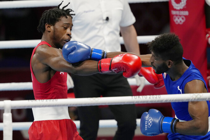 Keyshawn Davis, from the United States,left is punched by Cuba's Andy Cruz during their men's lightweight 63-kg boxing gold medal match at the 2020 Summer Olympics, Sunday, Aug. 8, 2021, in Tokyo, Japan. (AP Photo/Themba Hadebe)