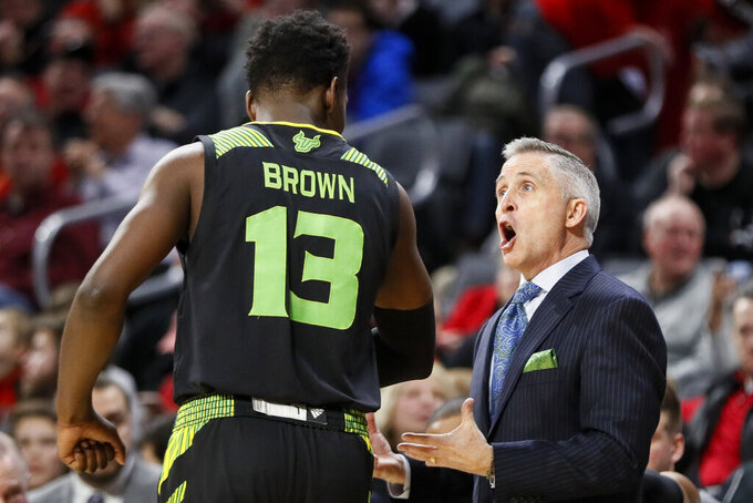 South Florida head coach Brian Gregory speaks with Justin Brown (13) in the first half of the team's NCAA college basketball game against Cincinnati, Tuesday, Jan. 15, 2019, in Cincinnati. (AP Photo/John Minchillo)