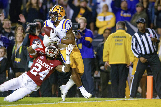 LSU wide receiver Ja'Marr Chase (1) catches a pass for a touchdown next to Arkansas defensive back LaDarrius Bishop (24) during the first half of an NCAA college football game in Baton Rouge, La., Saturday, Nov. 23, 2019. (AP Photo/Matthew Hinton)