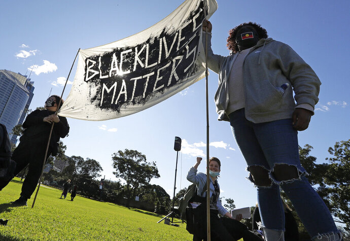 A couple hold a banner as thousands gather at a rally supporting the Black Lives Matter and Black Deaths in Custody movements in Sydney, Sunday, July 5, 2020. (AP Photo/Rick Rycroft)