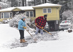 Worley and Sonja Parton, of Hinsdale, N.H., shovel their driveway together after an early morning snowstorm on Thursday, Jan, 16, 2020. A snowstorm dumped more than a half-foot of heavy snow on parts of Maine, New Hampshire and Vermont on Thursday, and it'll be followed by plunging temperatures and blustery winds.  (Kristopher Radder/The Brattleboro Reformer via AP)