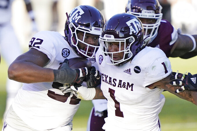 Texas A&M defensive lineman Jayden Peevy (92) recovers a fumble and is escorted downfield by linebacker Buddy Johnson (1) during the second half of an NCAA college football game in Starkville, Miss., Saturday, Oct. 17, 2020. Peevy did not score.  (AP Photo/Rogelio V. Solis)