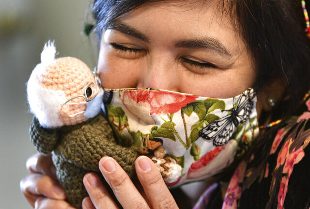 Tobey King, of Corpus Christi, Texas, embraces the crochet Bernie Sanders doll that she made and sold on eBay for $20,300 on Tuesday, Jan. 26, 2021. All of the proceeds are being donated to Meals on Wheels. (Billy Calzada/The San Antonio Express-News via AP)