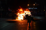 A police car burns during a protest in response to the police shooting of Walter Wallace Jr., late Monday, Oct. 26, 2020, in Philadelphia. Police officers fatally shot the 27-year-old Black man during a confrontation Monday afternoon in West Philadelphia that quickly raised tensions in the neighborhood. (Jessica Griffin/The Philadelphia Inquirer via AP)