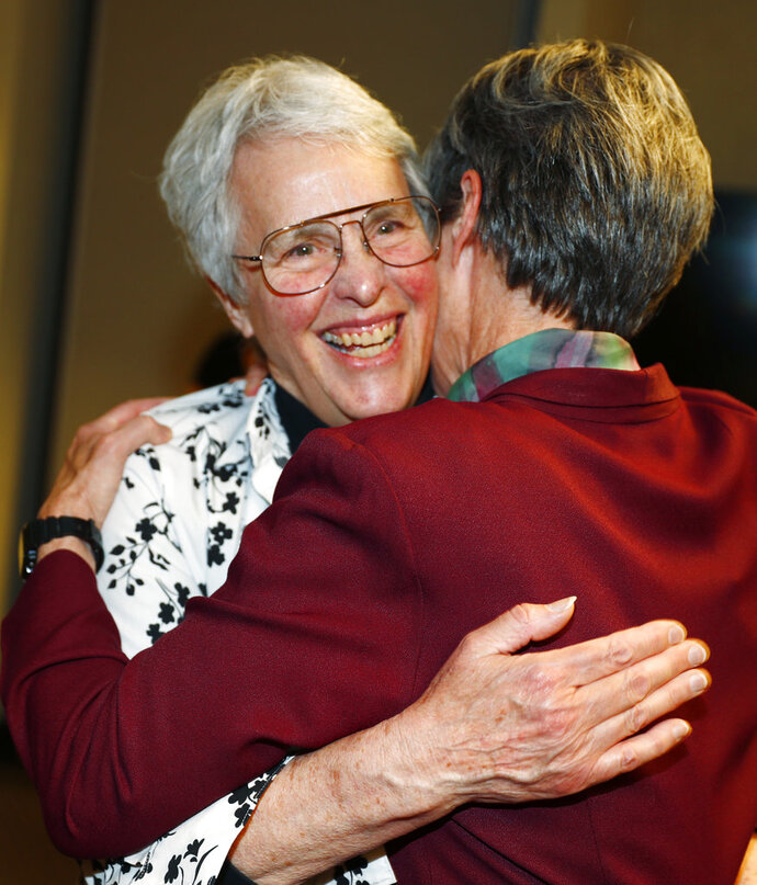 Professor Lucy Marsh, left, is hugged by fellow law professor K.K. DuVivier after an announcement that a judge has indicated support for a $2.66-million settlement in a lawsuit against the University of Denver law school on behalf of the two and five other female law professors who were paid less than their male colleagues at a news conference Thursday, May 17, 2018, in Denver. Marsh filed a complaint with the Equal Employment Opportunity Commission, which prompted the agency to review the dispute and file the suit. (AP Photo/David Zalubowski)