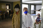 FILE - In this Jan. 14, 2021 file photo, residents, some reflected in a mirror, left, stand in their building's common area as they wait to get free, rapid COVID-19 tests during a volunteer testing campaign amid the new coronavirus pandemic, in the El Paraiso neighborhood of Caracas, Venezuela. The government of President Nicolás Maduro and the U.S.-backed opposition are accusing each other of playing politics with proposals to finance United Nations-supplied vaccines. (AP Photo/Matias Delacroix, File)