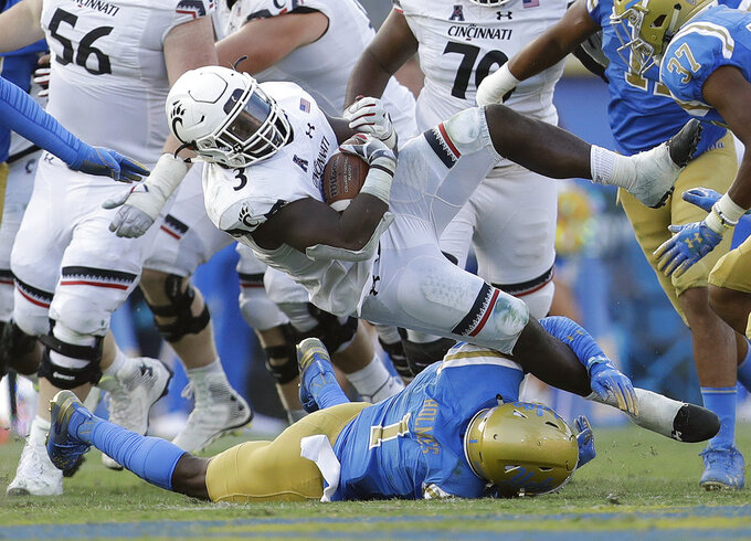 Cincinnati running back Michael Warren II, top, is tackled by UCLA defensive back Darnay Holmes (1) during the second half of an NCAA college football game Saturday, Sept. 1, 2018, in Pasadena, Calif. (AP Photo/Marcio Jose Sanchez)