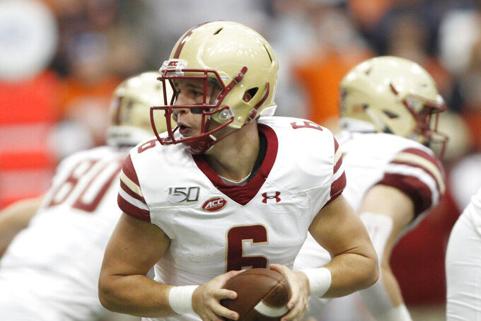 Boston College's Dennis Grosel looks to hand the ball off during the first quarter of an NCAA college football game against Syracuse in Syracuse, N.Y., Saturday, Nov. 2, 2019. (AP Photo/Nick Lisi)