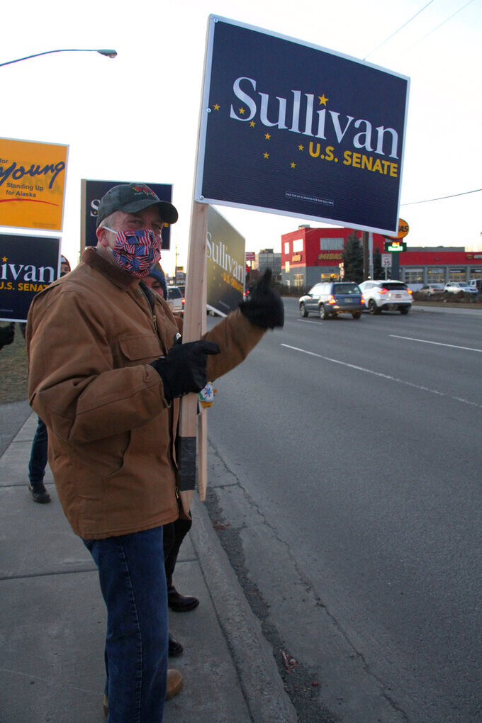 U.S. Sen. Dan Sullivan, an Alaska Republican seeking reelection, waves a sign at a busy intersection Monday, Nov. 2, 2020, in Anchorage, Alaska. Sullivan on Nov. 3, 2020, election faces Dr. Al Gross, an independent who won the Alaska Democratic primary. (AP Photo/Mark Thiessen)