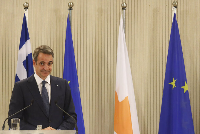 This image provided from Cyprus' press and information office, Greece's Prime minister Kyriakos Mitsotakis is seen during a press conference after a meeting with Cyprus President Nicos Anastasiades at the presidential palace in capital Nicosia, Cyprus, on Monday, Feb. 8, 2021. Mitsotakis is in Cyprus for one-day official visit. (Stavros Ioannides, PIO via AP)