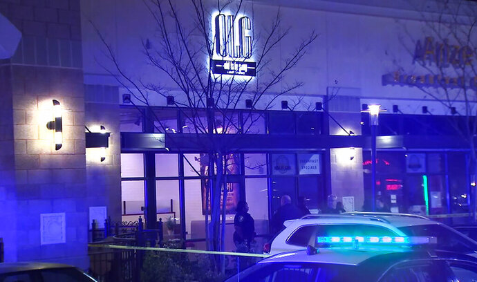 "In this image from video provided by WSB-TV, police officers stand outside Old Lady Gang restaurant Friday, Feb. 14, 2020, in East Point, Ga. Three people were shot and wounded at the restaurant just outside Atlanta that's owned by singer and ""Real Housewives of Atlanta"" star Kandi Burruss. A man entered the Old Lady Gang restaurant and targeted another man, East Point police Capt. Allyn Glover told news outlets. Police say two bystanders were also shot, and all three shooting victims suffered non-life-threatening injuries. (WSB-TV via AP)"