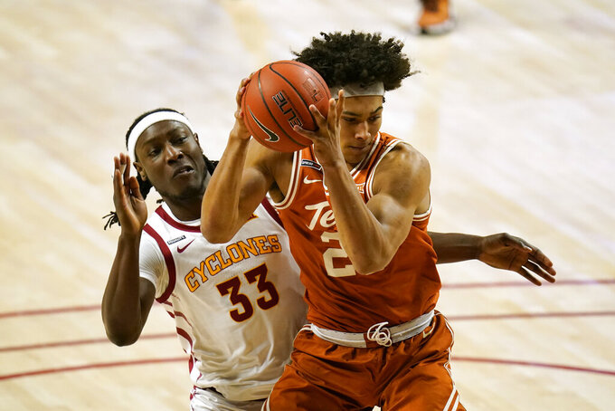 Texas forward Jericho Sims is fouled by Iowa State forward Solomon Young (33) during the first half of an NCAA college basketball game, Tuesday, March 2, 2021, in Ames, Iowa. (AP Photo/Charlie Neibergall)