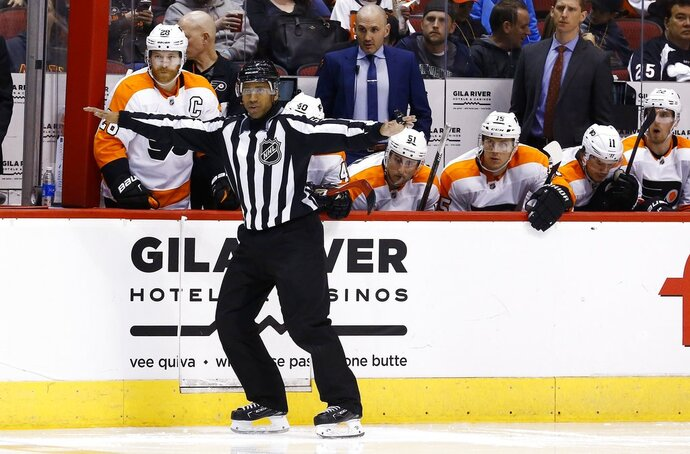Linesman Shandor Alphonso signals a clean transition across the blue line during the third period of an NHL hockey game between the Arizona Coyotes and the Philadelphia Flyers Saturday, Feb. 10, 2018, in Glendale, Ariz. The NHL has almost two dozen black players but just one black official in linesman Shandor Alphonso and one black coach in Flames assistant Paul Jerrard. Alphonso, Jerrard and recently retired linesman Jay Sharrers hope they can show young minorities they can stay in hockey beyond playing. (AP Photo/Ross D. Franklin)