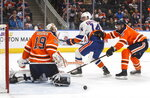 New York Islanders' Tom Kuhnhackl (14) is stopped by Edmonton Oilers goalie Mikko Koskinen (19) as Oilers' Adam Larsson (6) defends during first-period NHL hockey game action in Edmonton, Alberta, Thursday, Feb. 21, 2019. (Jason Franson/The Canadian Press via AP)