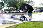 Franklin Castellon, 76, shields himself from the rain as he walks to an early voting site, Monday, Oct.19, 2020, in Miami. Florida begins in-person early voting Monday in much of the state as the Trump campaign tries to cut into an early advantage Democrats have posted in mail-in votes in the key swing state. (AP Photo/Lynne Sladky)