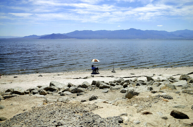 FILE - In this April 30, 2015 file photo, a man fishes along the receding banks of the Salton Sea near Bombay Beach, Calif. Scientists say that half of the world's sandy beached are at risk of disappearing by the end of the century if climate changes continues unchecked. Researchers at the European Union's Joint Research Center in Ispra, Italy, used satellite images to track the way beaches changed over the past 30 years and project how global warming might affect them in the future. (AP Photo/Gregory Bull, File)