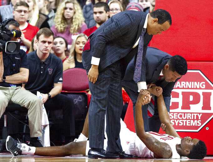 North Carolina State coach Kevin Keatts, left, helps Markell Johnson (11) up from the floor after Johnson suffered an injury during the first half of an NCAA college basketball game against Pittsburgh in Raleigh, N.C., Saturday, Jan. 12, 2019. (AP Photo/Ben McKeown)