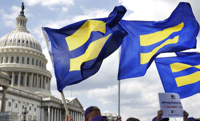 """FILE - In this July 26, 2017 file photo, people with the Human Rights Campaign hold up """"equality flags"""" during an event on Capitol Hill in Washington, in support of transgender members of the military. Defense officials say the Pentagon will sweep away Trump-era policies that largely banned transgender people from serving in the military and will issue new rules that broaden their access to medical care and gender transition. (AP Photo/Jacquelyn Martin, File)"""
