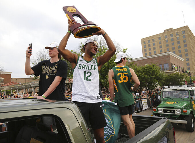 Baylor guard Jared Butler holds the NCAA Division I men's basketball tournament trophy as he is escorted down Austin Avenue with teammates Tuesday, April 13, 2021, in Waco, Texas. (Jerry Larson/Waco Tribune Herald via AP)