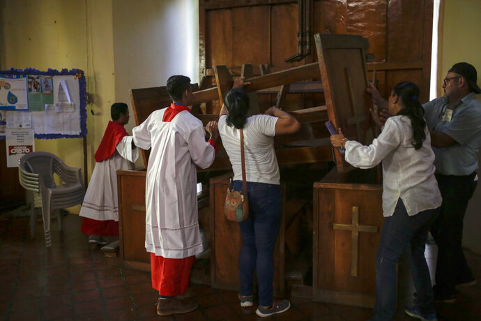 Altar boys and parishioners barricade one of the entrances of the San Juan Bautista Church after supporters of President Daniel Ortega attempted to enter the church by force, in Masaya, Nicaragua, Thursday, Nov. 21, 2019. The pro-Ortega group disrupted a mass in support of a group of mothers who are engaged in a hunger strike at the San Miguel Church in Masaya, to demand the release of their sons and daughters who are imprisoned by the Ortega government. (AP Photo/Alfredo Zuniga)