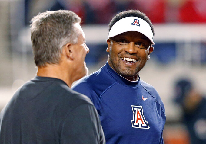 Arizona head coach Kevin Sumlin, right, and Utah coach Kyle Whittingham smile before an NCAA college football game Friday, Oct. 12, 2018, in Salt Lake City. (AP Photo/Rick Bowmer)
