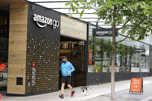 A person wearing a mask jogs past an Amazon Go store, Thursday, April 30, 2020, in downtown Seattle. Amazon.com is expected to announce earnings for the first quarter of 2020 at the close of markets Thursday, a report that is expected to be closely watched due to the effects of the coronavirus outbreak on the company. (AP Photo/Ted S. Warren)