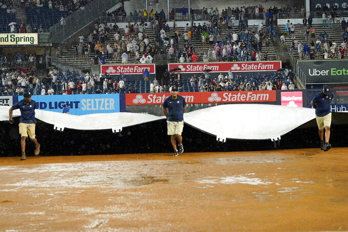 The grounds crew roll out the tarp during a rain delay after sixth inning of a baseball game between the New York Yankees and the Boston Red Sox, Saturday, July 17, 2021, in New York. (AP Photo/Mary Altaffer)