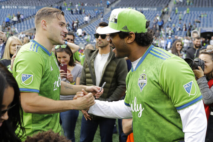 Seattle Sounders forward Jordan Morris, left, greets Sounders minority owner and NFL football Seattle Seahawks quarterback Russell Wilson, right, after an MLS soccer match against Minnesota United, Sunday, Oct. 6, 2019, in Seattle. The Sounders won 1-0. (AP Photo/Ted S. Warren)