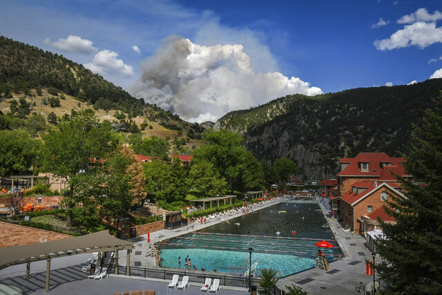 Smoke from the Grizzly Creek fire billows behind the Glenwood Hot Springs Pool in Glenwood Canyon after the fire blew up again, Wednesday, Aug. 12, 2020, near Glenwood Springs, Colo. (Chelse Self/Glenwood Springs Post Independent via AP)