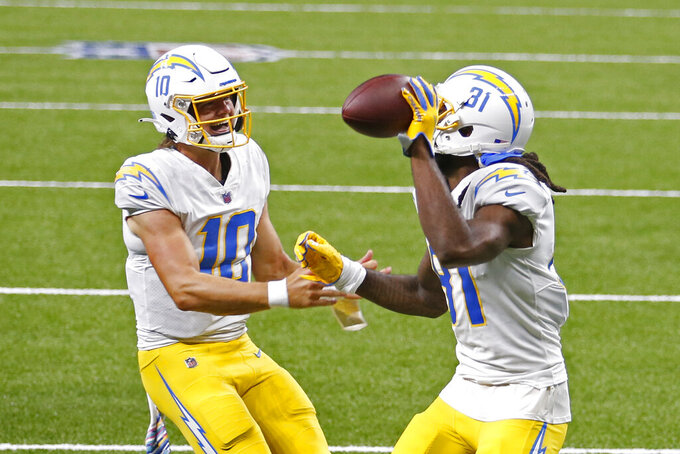 Los Angeles Chargers wide receiver Mike Williams (81) celebrates his touchdown reception with quarterback Justin Herbert (10) in the first half of an NFL football game against the New Orleans Saints in New Orleans, Monday, Oct. 12, 2020. (AP Photo/Brett Duke)