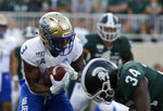 Tulsa's Shamari Brooks, left, is hit behind the line of scrimmage by Michigan State's Antjuan Simmons (34) on a pass reception during the first quarter of an NCAA college football game, Friday, Aug. 30, 2019, in East Lansing, Mich. (AP Photo/Al Goldis)