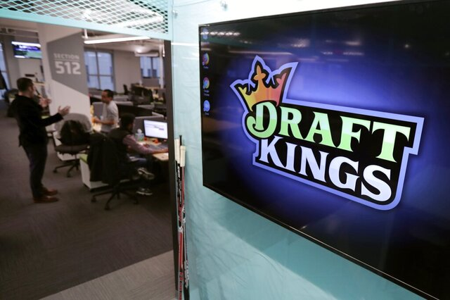FILE - In this May 2, 2019, file photo, the DraftKings logo is displayed at the sports betting company headquarters in Boston. DraftKings announced Monday, Dec. 23 it is merging with two companies and taking its stock public. It will retain the DraftKings moniker and complete its merger with gambling tech firm SBTech sometime in the first half of 2020. (AP Photo/Charles Krupa, File)