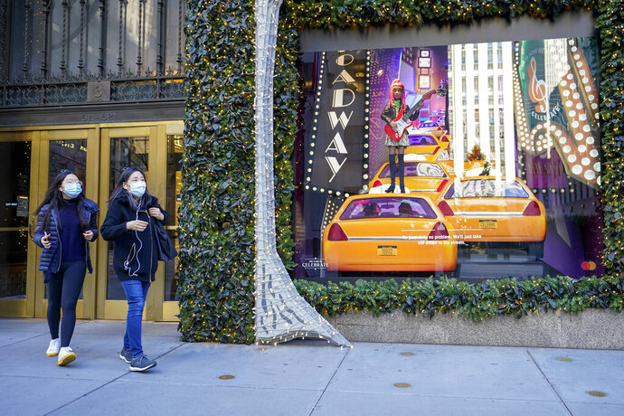 Black Friday shoppers wear face masks as the leave Saks Fifth Avenue flagships store empty handed, Friday, Nov. 27, 2020, in New York. (AP Photo/Mary Altaffer)