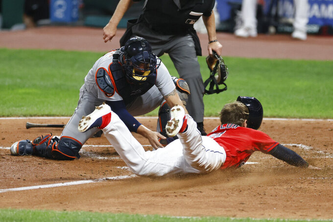 Cleveland Indians' Jordan Luplow, right, scores past Detroit Tigers' Austin Romine on a double by Domingo Santana during the sixth inning of a baseball game, Saturday, Aug. 22, 2020, in Cleveland. (AP Photo/Ron Schwane)