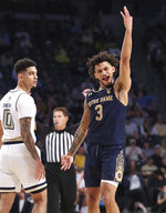 Notre Dame guard Prentiss Hubb reacts to hitting a 3-pointer, next to Georgia Tech guard Michael Devoe in the final minutes of Notre Dame's win in an NCAA college basketball game Wednesday, Jan. 15, 2020, in Atlanta. (Curtis Compton/Atlanta Journal-Constitution via AP)