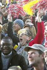 Parade spectators cheer for the television cameras at the 131st Rose Parade in Pasadena, Calif., Wednesday, Jan. 1, 2020. (AP Photo/Michael Owen Baker)
