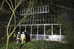 Firefighters stand in front of a burnt out animal house at the Krefeld Zoo in Krefeld, Germany, early Wednesday, Jan. 1, 2020. A large number of animals in the building included chimpanzees, orangutans and two gorillas, as well as fruit bats and birds are dead. (David Young/dpa via AP)
