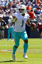 Miami Dolphins quarterback Tua Tagovailoa points to a teammate as he runs with the ball during the first half of an NFL preseason football game against the Chicago Bears in Chicago, Saturday, Aug. 14, 2021. (AP Photo/Nam Y. Huh)