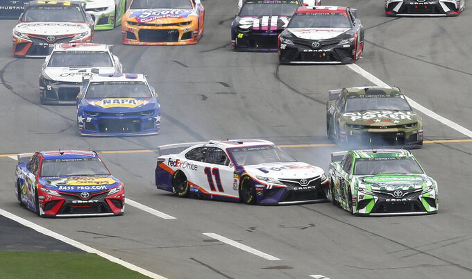 Denny Hamlin (11) makes contact with Kyle Busch, front right, during the NASCAR Cup Series auto race at Daytona International Speedway, Sunday, July 7, 2019, in Daytona Beach, Fla. Both drivers were able to continue with the race. (AP Photo/David Graham)