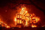 Flames from the Glass Fire consume the Black Rock Inn, late Sunday, Sept. 27, 2020, in St. Helena, Calif. (AP Photo/Noah Berger)