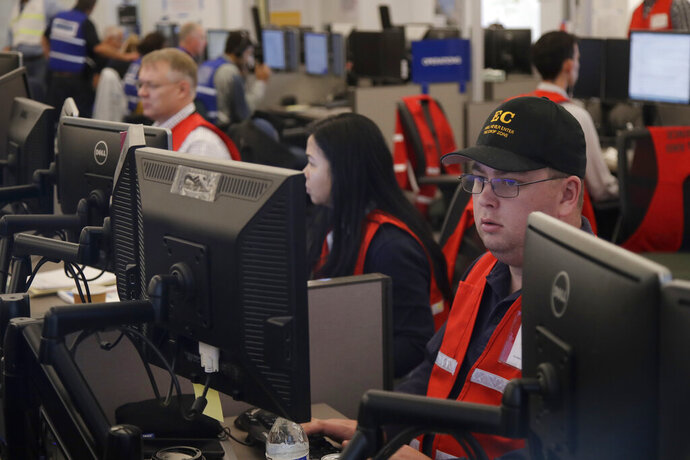 FILE - In this Oct. 10, 2019, file photo, Pacific Gas & Electric employees work in the PG&E Emergency Operations Center in San Francisco. Experts say it's hard to know what might have happened had the power stayed on, or if the utility's proactive shutoffs are to thank for California's mild fire season this year. (AP Photo/Jeff Chiu, File)