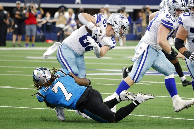 Dallas Cowboys tight end Dalton Schultz (86) is stopped after catching a pass by Carolina Panthers linebacker Shaq Thompson (7) in the first half of a NFL football game in Arlington, Texas, Sunday, Oct. 3, 2021. (AP Photo/Michael Ainsworth)