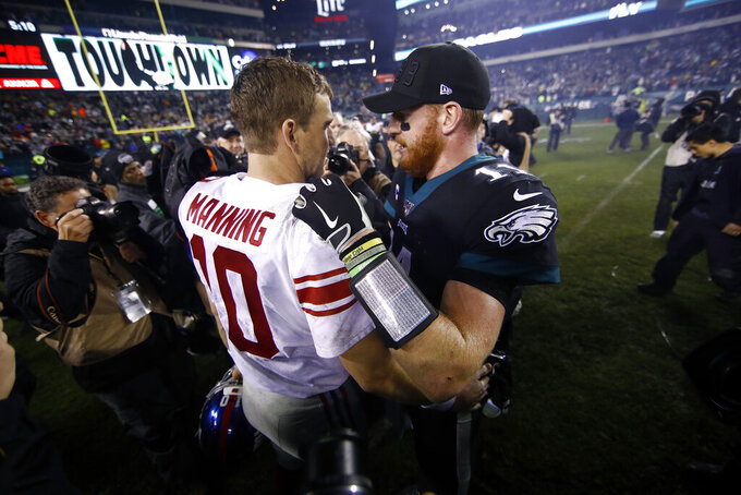New York Giants' Eli Manning, left, and Philadelphia Eagles' Carson Wentz meet after overtime of an NFL football game, Monday, Dec. 9, 2019, in Philadelphia. (AP Photo/Matt Rourke)