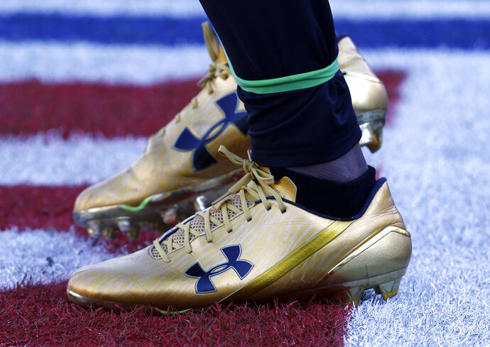 FILE- In this Dec. 10, 2017, file photo, Jacksonville Jaguars running back T.J. Yeldon warms up wearing Under Armour cleats before an NFL football game against the Seattle Seahawks in Jacksonville, Fla. Under Armour reports financial results Tuesday, Feb. 13, 2018. (AP Photo/Stephen B. Morton, File)