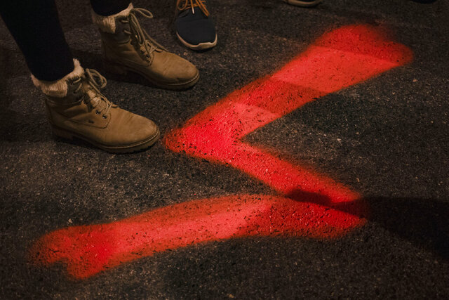 FILE - In this Wednesday, Nov. 18, 2020 file photo, demonstrators stand next to a red lightning bolt, a symbol of the pro-choice movement, painted on the pavement during a protest against a top court ruling restricting abortions in Warsaw, Poland. Prosecutors have opened an investigation into whether the Polish flag was publicly insulted after a family in Warsaw hung a flag from their balcony combined with a lightning bolt, a symbol for women's rights in Poland. (AP Photo/Agata Grzybowska, File)