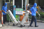 Medical workers wheel oxygen tanks at Dr. Sardjito Central Hospital in Yogyakarta, Indonesia, Sunday, July 4, 2021. A number of COVID-19 patients died amid an oxygen shortage at the hospital on the main island of Java following a nationwide surge of coronavirus infections. (AP Photo/Kalandra)