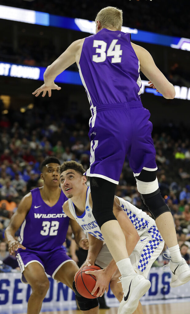Kentucky's Reid Travis, center, looks for a shot as Abilene Christian's Kolton Kohl (34) jumps high to defend during the first half of a first-round game in the NCAA men's college basketball tournament in Jacksonville, Fla. Thursday, March 21, 2019. (AP Photo/John Raoux)