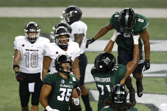 Hawaii running back Dae Dae Hunter (0) is lifted by offensive lineman Micah Vanterpool (71) after a touchdown against UNLV during the first half of an NCAA college football game Saturday, Dec. 12, 2020, in Honolulu. (AP Photo/Marco Garcia)